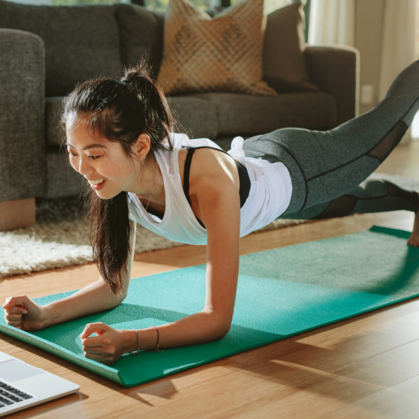 A woman does yoga while viewing a laptop.