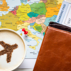 An airplane is in the foam of a cup of coffee on top of a map.