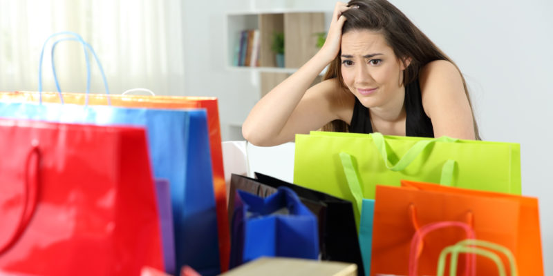 A woman looks upset as she gazes at packages she has purcahsed.